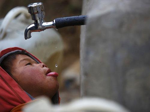 Một bé trai uống từng giọt nước ở vòi nước công cộng tại Nepal (Ảnh: Reuters)